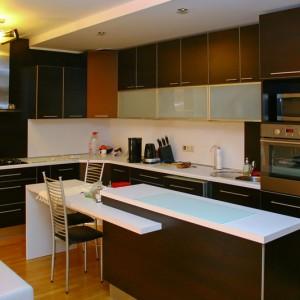 Tumši brūna iebūvētā virtuve ar baltu virsmu